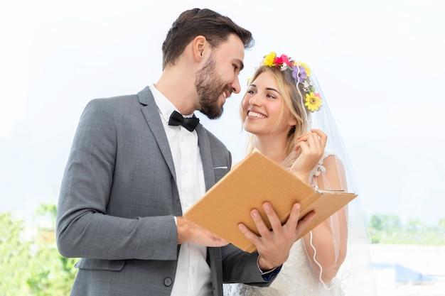 Couple De Jeunes Mariés De Race Blanche En Choisissant La Robe Dans Le Studio De Mariage. Photo Premium