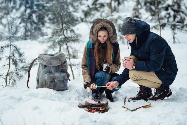 Couple de jeunes voyageurs rôtir des guimauves sur un feu de joie dans la forêt d'hiver enneigée Photo gratuit