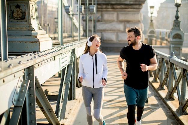 Couple jogging sur le pont des chaînes à budapest Photo Premium
