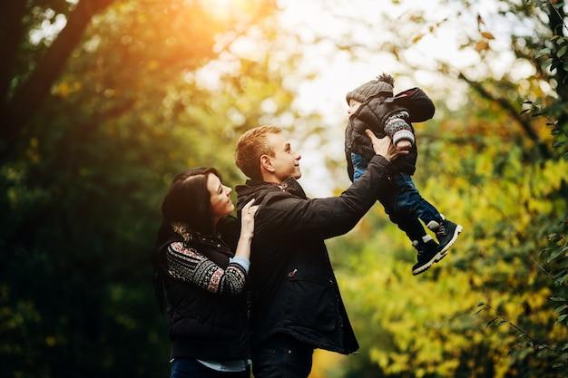 Couple jouant avec un enfant dans le parc Photo gratuit