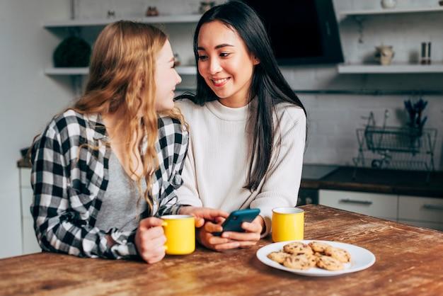 Couple lesbien assis à table avec smartphone Photo gratuit