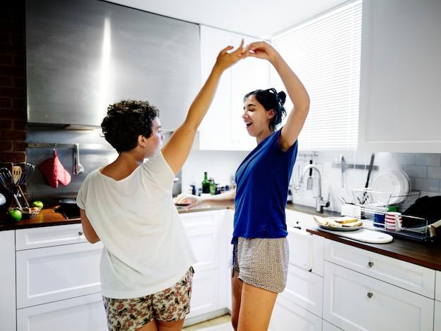 Couple lesbien danse dans la cuisine Photo Premium