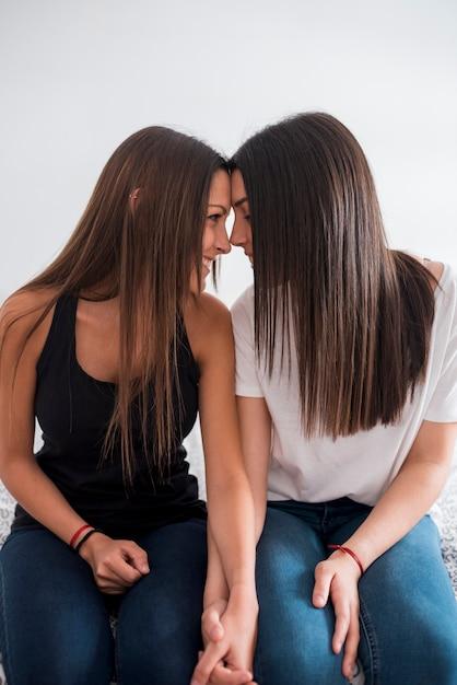Couple de lesbiennes assis tout en penchant le front Photo gratuit