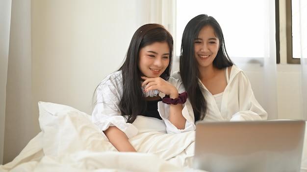 Un Couple De Lesbiennes Regarde Un Film Depuis Un Ordinateur Portable Assis Ensemble Sur Le Lit. Photo Premium