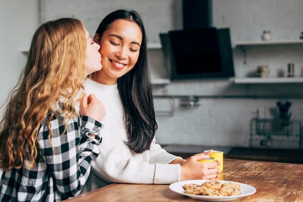 Couple de lesbiennes s'embrasser dans la cuisine Photo gratuit