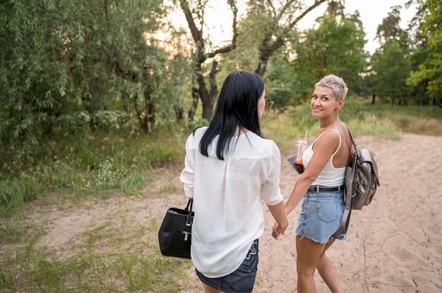 Couple De Lesbiennes Se Tenant La Main En Plein Air Photo gratuit