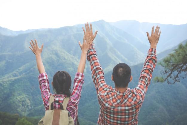 Le couple leva les mains au sommet de la colline dans la forêt tropicale. randonnée, voyages, escalade. Photo gratuit