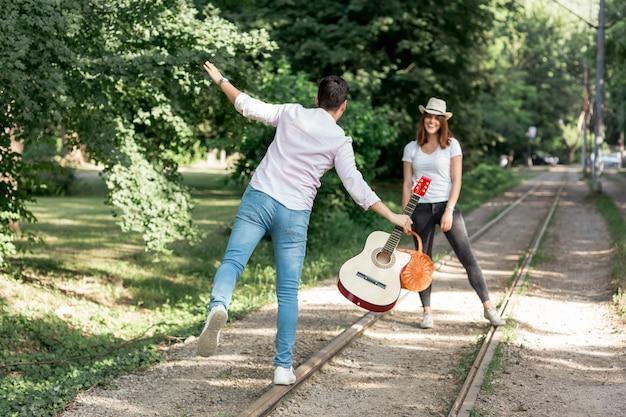 Couple ludique marchant sur un chemin de fer Photo gratuit