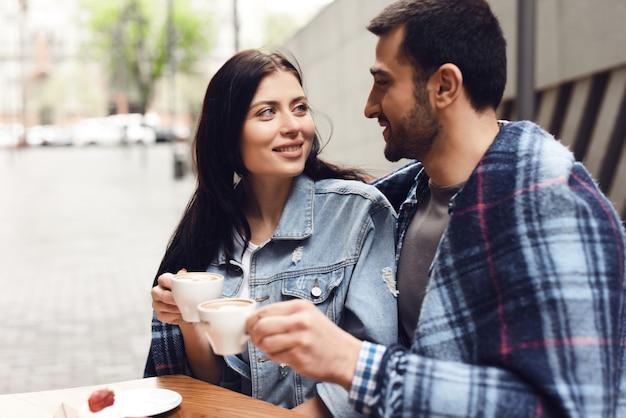 Couple en lune de miel dans un café enveloppé dans une couverture douillette. Photo Premium