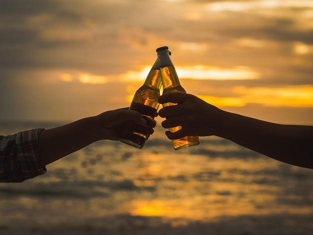 Couple mains tenant des bouteilles de bière et cliquetant sur la plage du coucher du soleil. Photo Premium