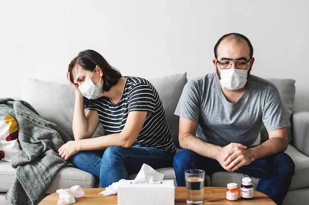 Couple malade assis sur le canapé Photo Premium