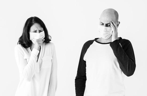 Couple malade portant un masque chirurgical Photo gratuit