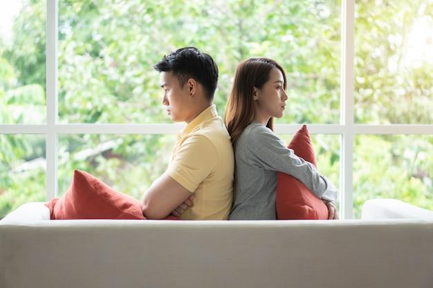 Couple malheureux assis l'un derrière l'autre sur le canapé et évite de parler Photo Premium