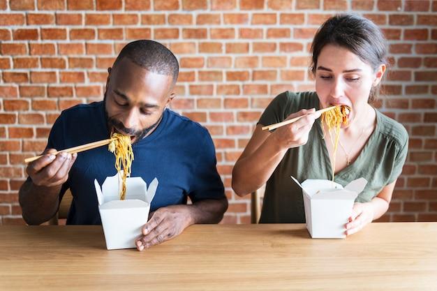 Couple mangeant chow mein ensemble Photo Premium