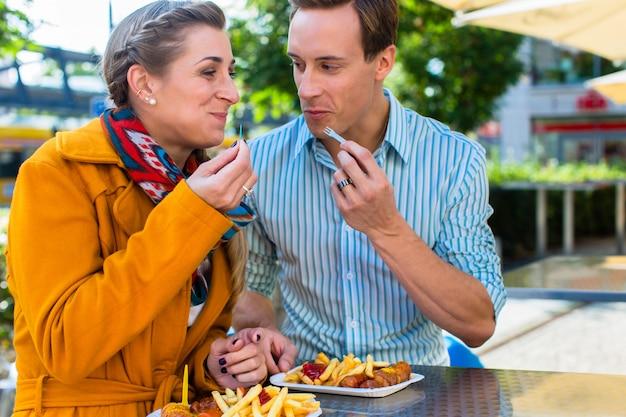 Couple mangeant une currywurst allemande au stand Photo Premium