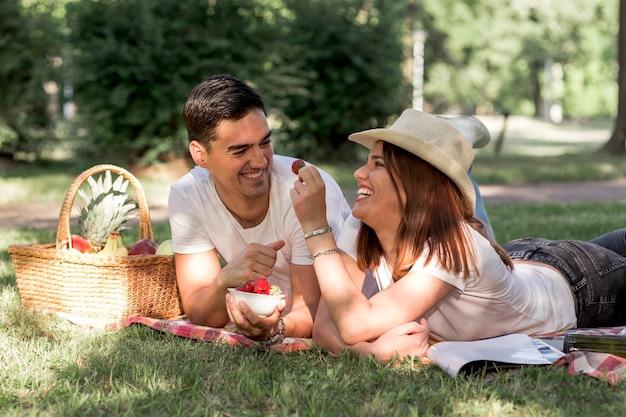 Couple mangeant des fraises au pique-nique Photo gratuit