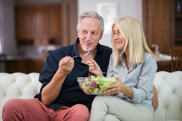 Couple mangeant une salade mixte dans leur appartement Photo Premium