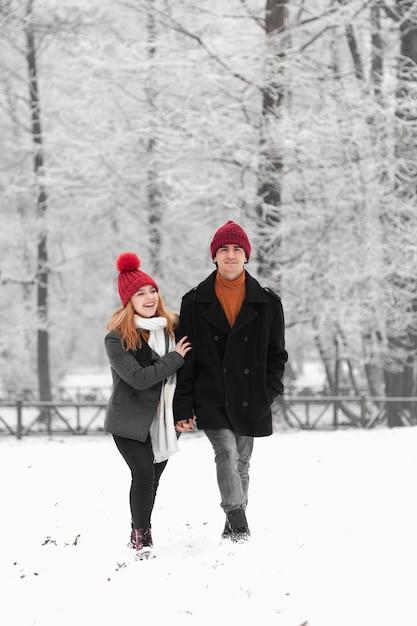 Couple Marchant Joyeusement Dans Un Parc Enneigé Gelé Photo gratuit