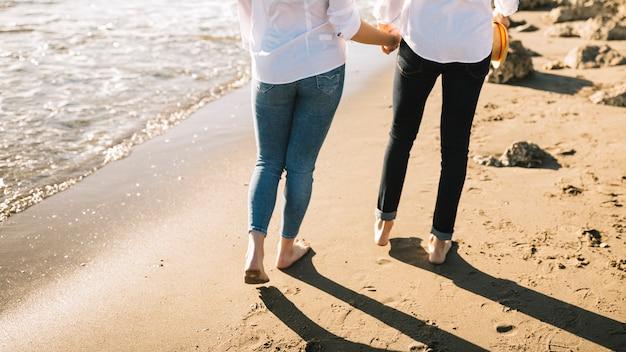 Couple marchant sur la plage Photo gratuit
