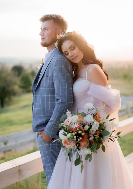 Couple De Mariage Dans La Chaude Soirée D'été Près De La Prairie Vêtue D'une Robe De Mariée Bohème Avec Un Beau Bouquet De Mariée Photo gratuit
