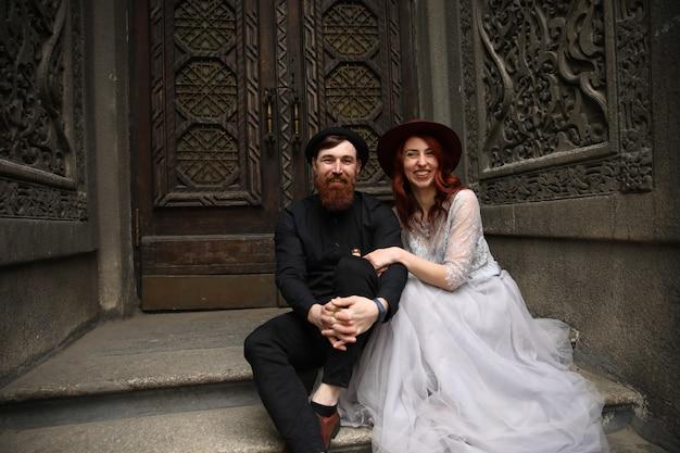 Couple De Mariage Extraordinaire Vêtu De Chapeaux Et De Tenues Formelles Est Assis Sur Les Escaliers En Pierre Et Souriant Photo gratuit