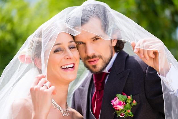 Couple de mariage mariée et le marié se cachent sous le voile Photo Premium