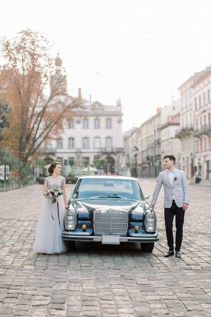 Couple De Mariage Romantique Debout Devant Une Voiture Rétro Noire, Belle Mariée Et Le Marié Heureux En été, Les Bâtiments De La Vieille Ville En Arrière-plan Photo Premium