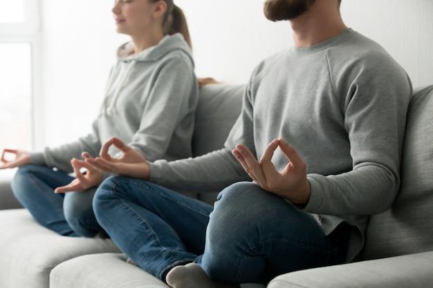 Couple, Méditer, Pratiquer, Yoga, à, Maison, Sofa, Concentrer, Mains Photo gratuit