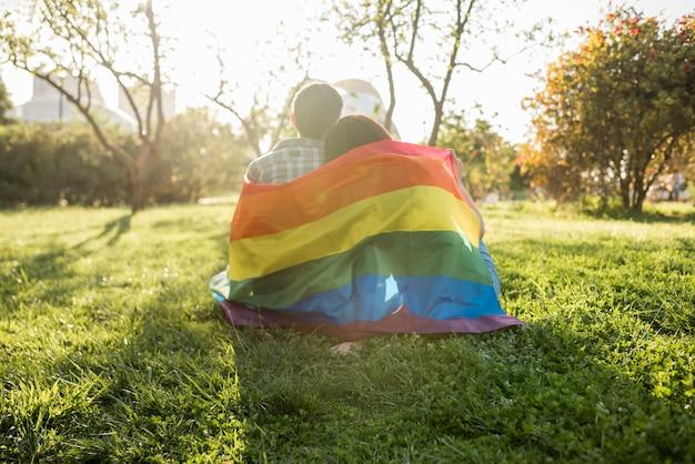 Un couple de même sexe dans le drapeau lgbt assis dans un parc Photo gratuit