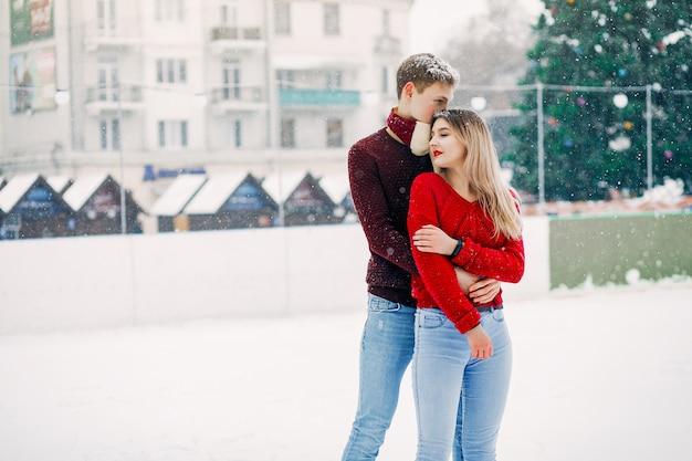 Couple mignon et affectueux dans un chandail rouge dans une ville d'hiver Photo gratuit
