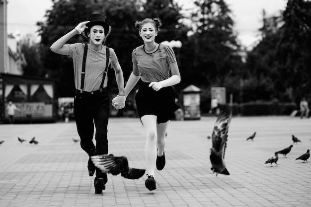 Couple de mime tenant les mains sur le trottoir Photo gratuit