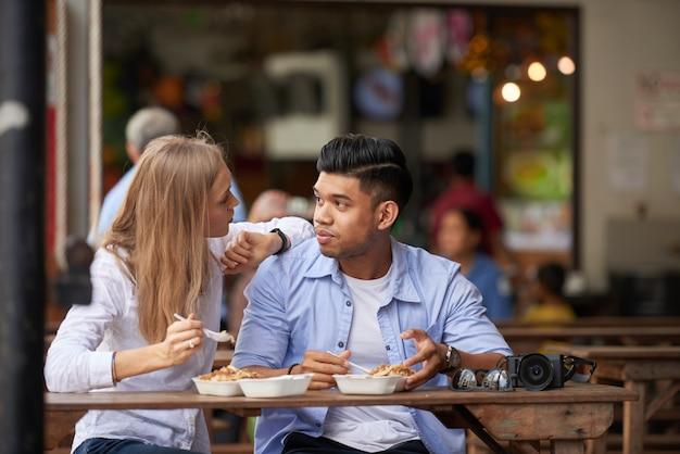 Couple mixte au café en plein air Photo gratuit