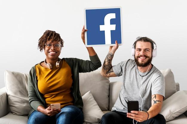 Couple montrant une icône facebook Photo gratuit