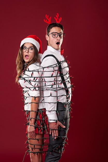 Couple De Nerd Drôle S'emmêle Dans Les Lumières De Noël Photo gratuit