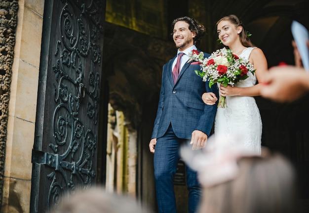 Couple nouvellement marié sortant de l'église Photo Premium
