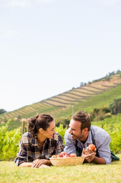Couple avec panier de pommes se détendre au vignoble Photo Premium
