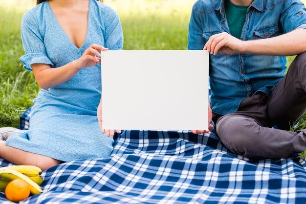Couple avec papier blanc assis sur une couverture Photo gratuit