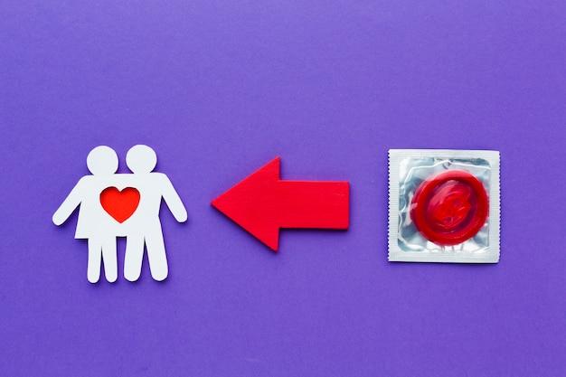 Couple De Papier à Côté Du Préservatif Rouge Photo gratuit