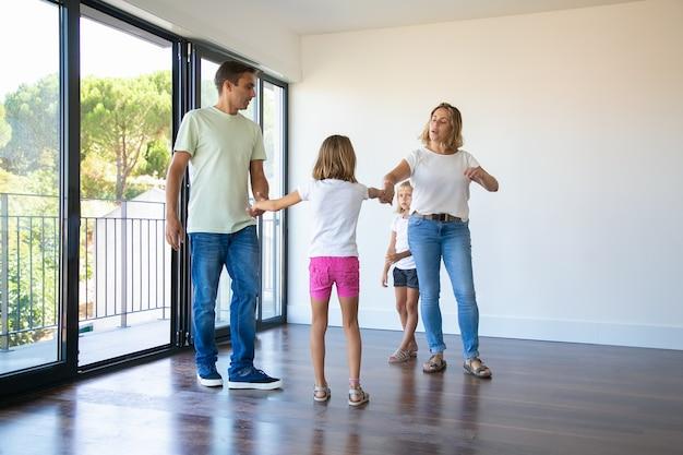 Couple De Parents Et Deux Enfants Profitant De Leur Nouvelle Maison, Debout Dans Une Pièce Vide Et Se Tenant La Main, Dansant Photo gratuit