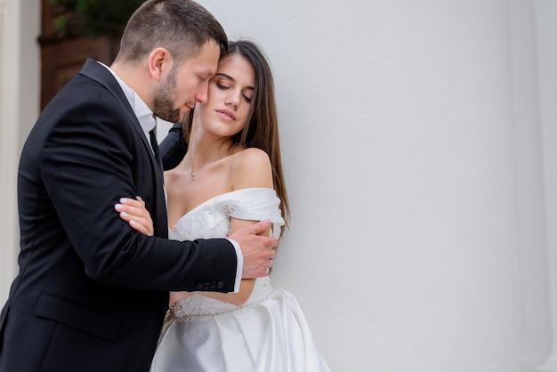 Couple Passionné En Tenue De Mariage Se Tient Près Du Mur Blanc, Concept De Mariage Photo gratuit