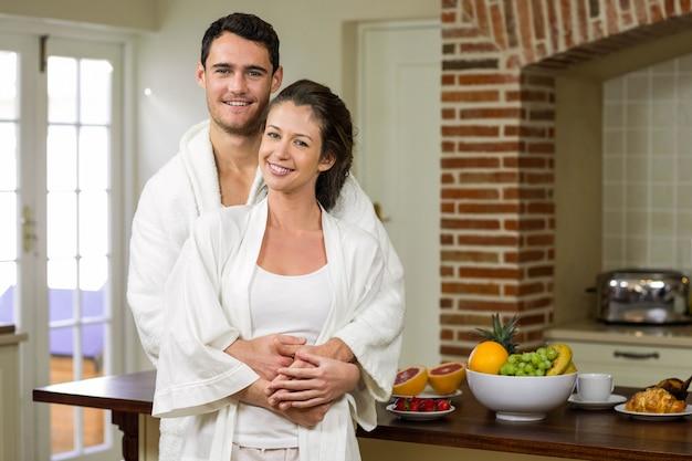 Couple en peignoir souriant tout en s'embrassant dans la cuisine Photo Premium