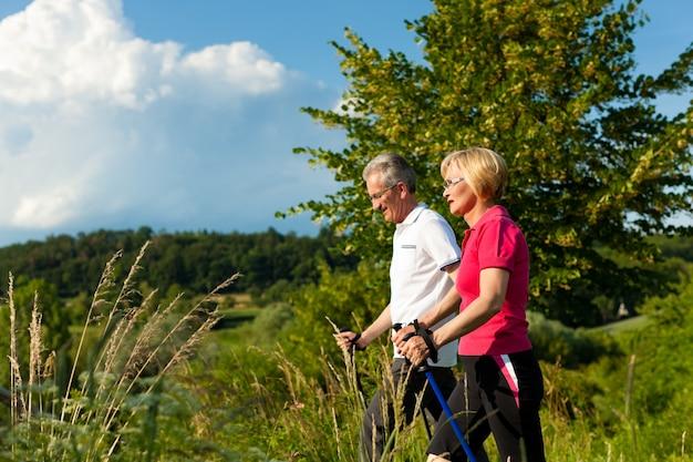Couple de personnes âgées actives en randonnée avec des bâtons de marche nordique Photo Premium