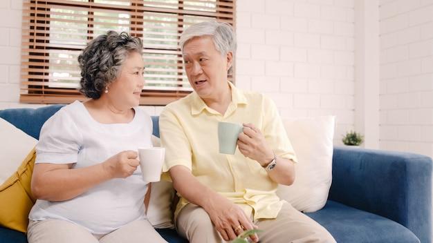 Couple de personnes âgées asiatique buvant un café chaud et discutant ensemble dans le salon à la maison, couple profitant d'un moment d'amour en position couchée sur un canapé pour une détente à la maison. Photo gratuit