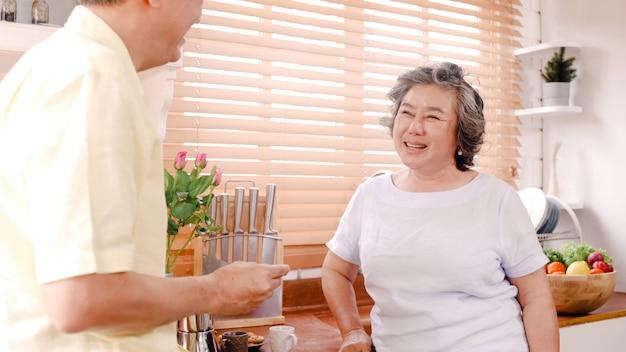 Couple de personnes âgées asiatique prenant son petit déjeuner dans la cuisine à la maison. couple de chinois doux donnant des biscuits à sa femme à la maison. Photo gratuit