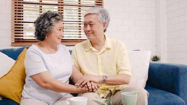 Couple de personnes âgées asiatique tenant leurs mains tout en prenant ensemble dans le salon, un couple se sentant heureux de partager et se soutenir mutuellement allongé sur un canapé à la maison. Photo gratuit