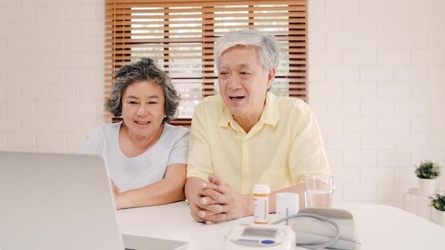 Couple de personnes âgées asiatique utilisant la conférence de l'ordinateur portable avec médecin sur les informations de médecine dans le salon, couple utilisant le temps ensemble en position couchée sur le canapé à la maison. Photo gratuit