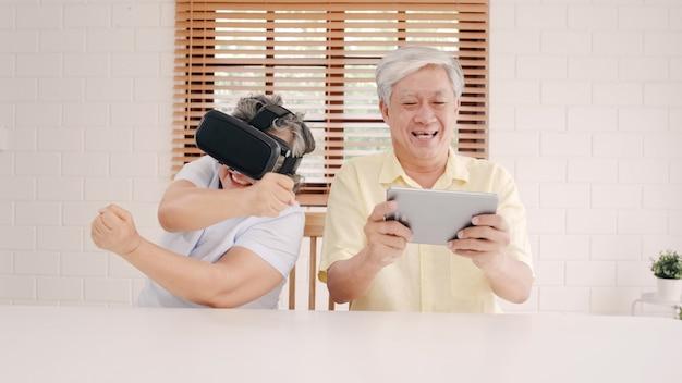 Couple De Personnes âgées Asiatique Utilisant Une Tablette Et Un Simulateur De Réalité Virtuelle, Jouant à Des Jeux Dans Le Salon, Un Couple Se Sentant Heureux De Passer Du Temps Sur La Table à La Maison. Photo gratuit