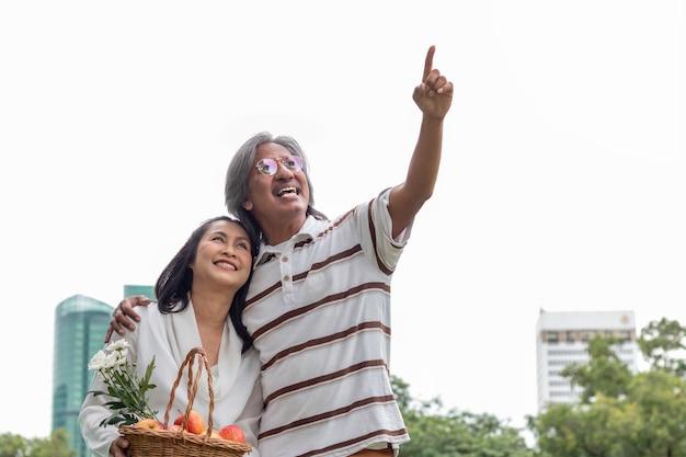 Couple De Personnes âgées Asiatiques Avec Bonheur De Style De Vie Panier De Fruits Dans Le Parc. Photo Premium