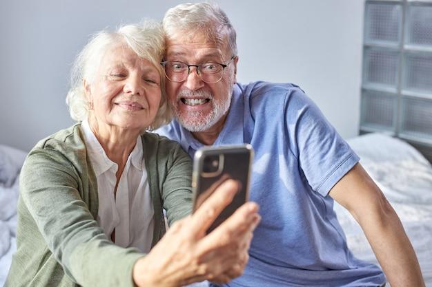 Couple De Personnes âgées Assis Sur Un Canapé En Prenant Des Photos Sur Smartphone, Posant Au Téléphone, Profitant Du Temps Le Week-end. Concept De Famille, Technologie, âge Et Personnes Photo Premium