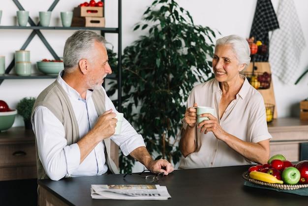 Couple de personnes âgées assis dans la cuisine, appréciant le café Photo gratuit